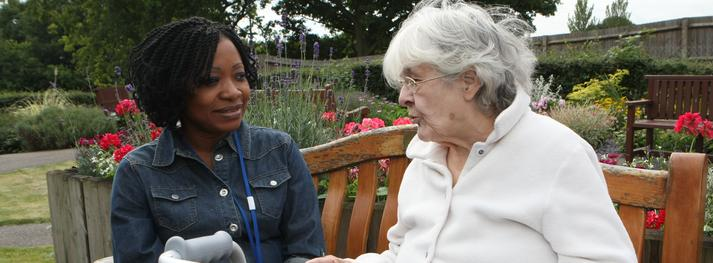 Older adult in garden with nurse