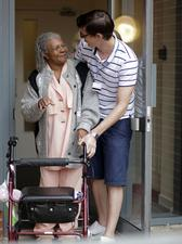 News photo of a patient and helper outside a Greenwich Community Health Services facility