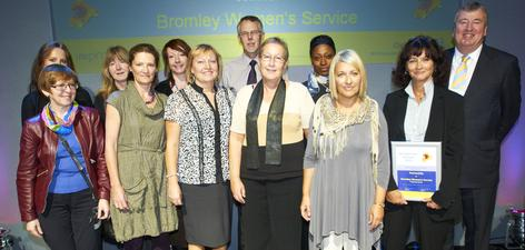 News: Maggie Schaedel (holding certificate) and The Bromley Woman's Service picking up the Partnership award at the 2010 AMM.